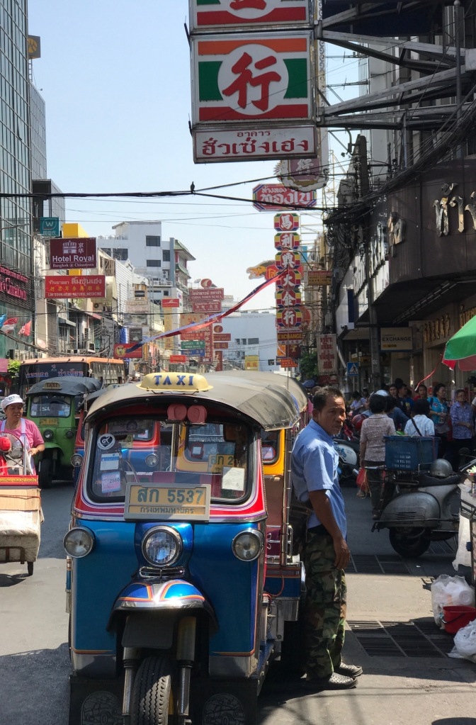 A tuktuk and its driver on the streets of Chinatown, Bangkok
