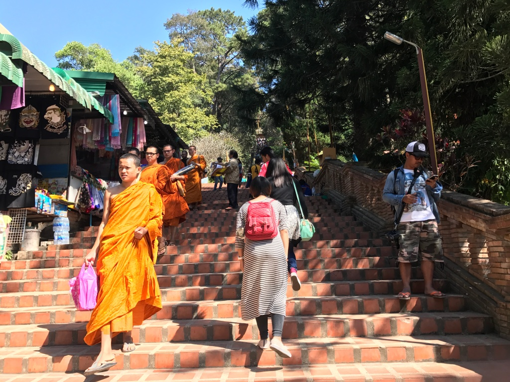 Monks seen walking down the stairs passed the market outside of the Wat Phra That Doi Suthep. Photo credit: Aaron.